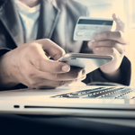 Man Holding A Credit Card and Cell Phone